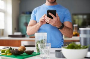 A man looking at a smartphone. Before him is diced produce, some in a blender cup