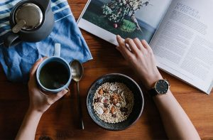 A person enjoying breakfast while reading a magazine